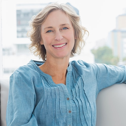 An mature woman with short hair wearing a blue shirt smiling brightly to show that this dentist in Loganville GA, can restore your smile with dental implants for all