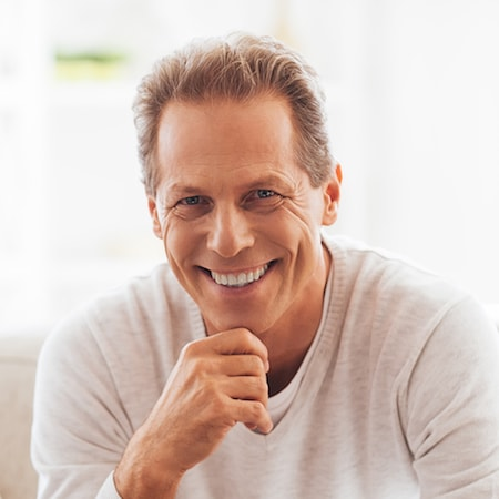 Man in white sweater smiling about the effect his dental implant has had on his life.