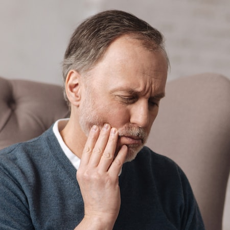 Man holding a painful jaw that needs treatment for TMJ.
