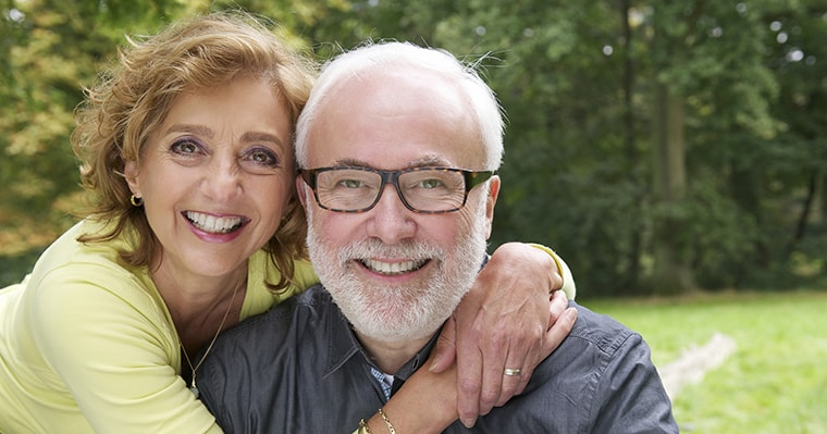 A husband and wife with implant retained dentures smiling with greenery behind them
